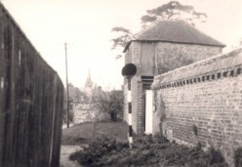 Looking out from the start of a 'twitten', a small lane between wall and fence, which joins the area you can see to the park, in Hurstpierpoint, Sussex, England