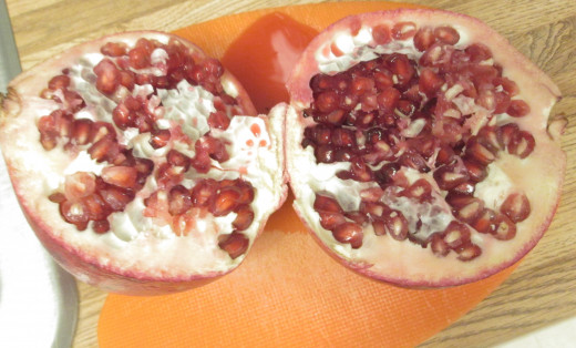 The pomegranate is divided in half to display the beautiful arils, which are filled with fruit juice and the seeds.