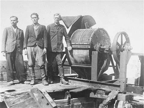 A Sonder Kommando Unit in 1943 with a reported bone crushing machine at the Janowska camp.  Source Wikipedia.
