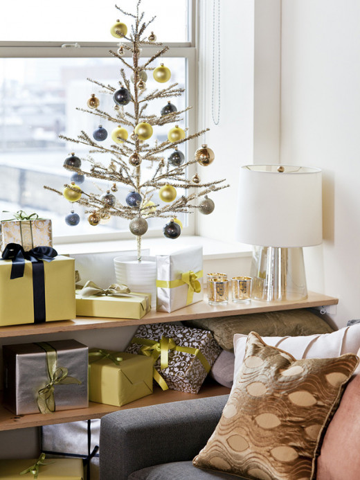 a small table top tree with ornaments and wrapped presents in coordinating colors makes for a