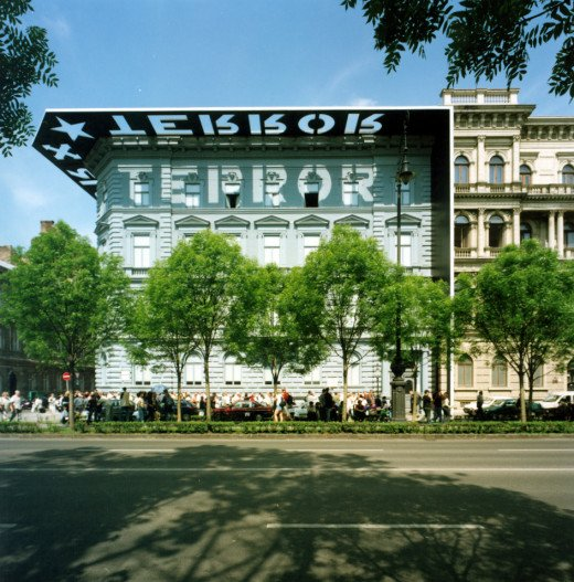 The house of terror, with the specially designed facade, casting the text 'Terror' on the wall along with an arrow cross and a star.