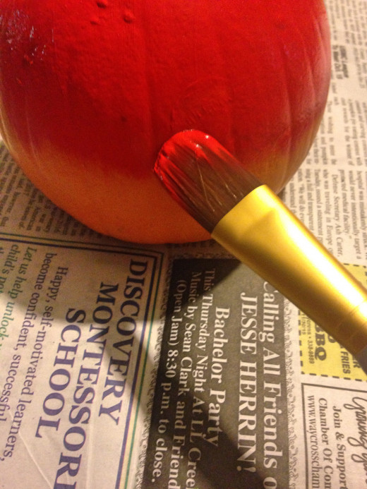 Use a large paintbrush to cover the pumpkin in red paint. Let it dry completely before continuing.