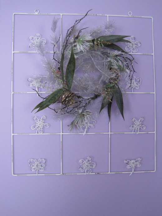 A festive wreath hung on a white photo rack.