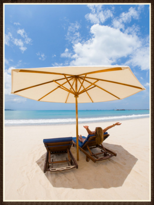 Stop the sun from damaging your skin. One way: Cover up with a beach umbrella.