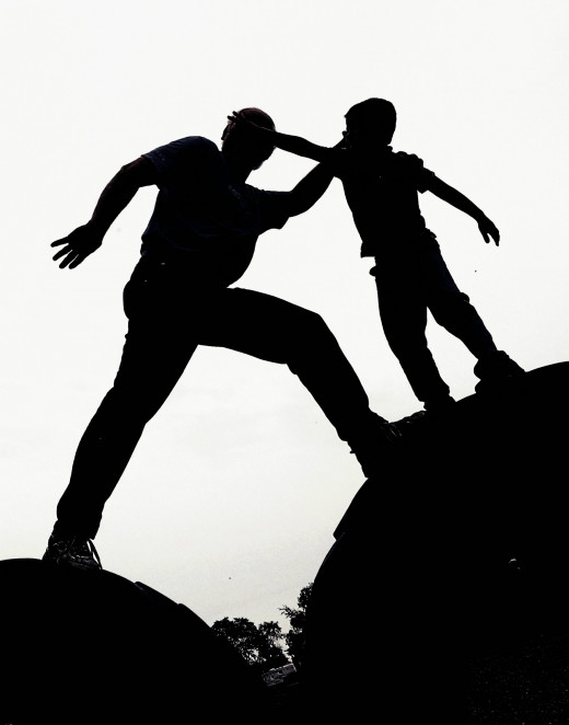 Silhouette of a father assisting a son while climbing.