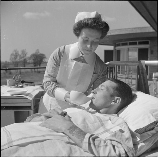 A nurse uses a spouted cup to feed a patient in the sunshine of an open air 'ward' of Broomfield Sanatorium, Chelmsford. This patient has been ordered complete bed rest, and so cannot sit up to drink.
