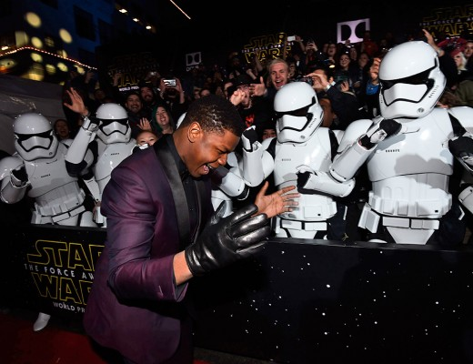 Finn wearing a black glove, with Stormtroopers at the Star Wars: The Force Awakens World Premiere.