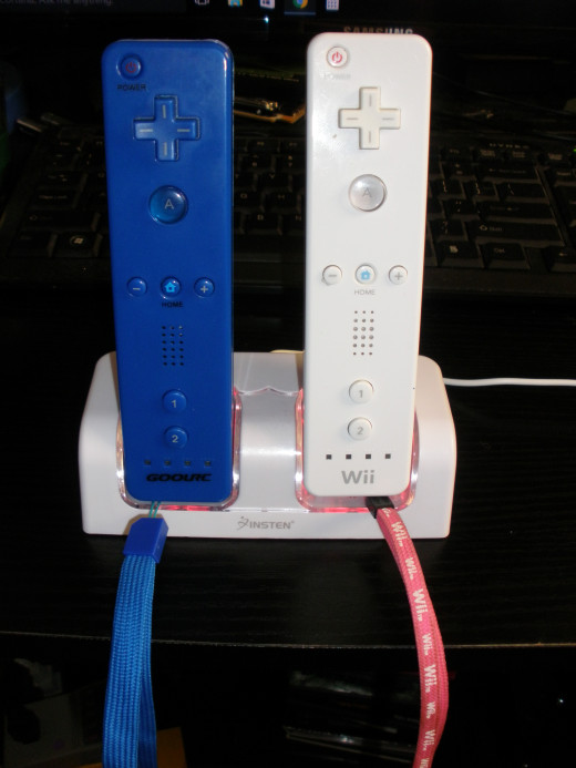 My Insten branded Wii remote charger base, battery packs installed in remotes and charging.