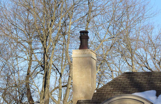 Close-up of copper chimney pot atop a masonry chimney on a clear winter's day.