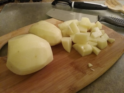 Peel and chop 2-3 large potatoes into 1/2 inch cubes. All purpose white potatoes are best, but you can use whatever you have on hand.