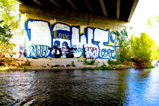 Graffiti marks the walls under the bridge.