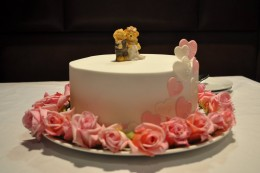 Our single tier cake decorated with roses from a friend's garden and a cake topper bought off a website similar to Craig's List.