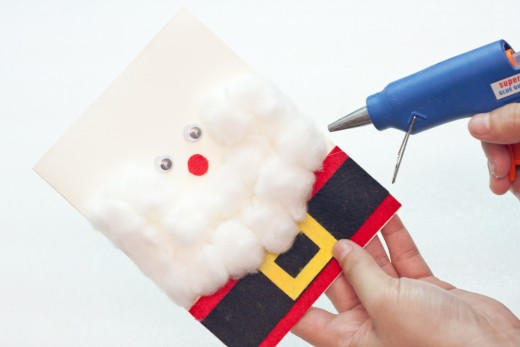 Step 13.  Continue gluing cotton balls on the sides and along Santa's neck area.  He is, after all, known for his lush, thick, long white beard..