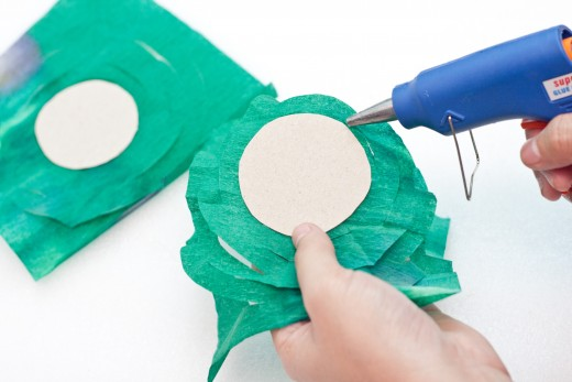 Unfold the green crepe paper into a square.  Glue the cardboard circle in the center of your square.
