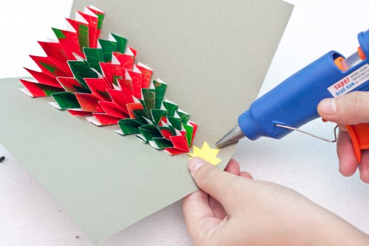 Cut a star out of the yellow construction paper and top your tree with it.