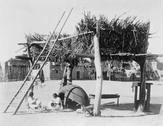 1915 photo of Zuni women crafting pottery under a drying rack for maize and other foods. Note the horno (outdoor adobe oven) which serves a dual purpose: drying the plants and to glaze the pottery.