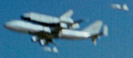 The Space Shuttle Columbia atop a Boeing 747 flying over Kelly AFB, TX with 2 T-38 chase planes.    The Space Shuttle used heat tiles that could absorb tremendous amounts of heat and still be cool to the touch.