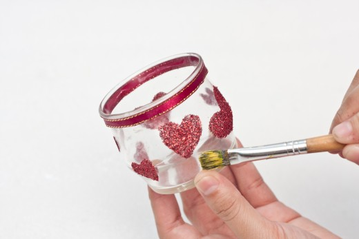 Brush the un-glittered areas of the candle holder with a paint brush to remove any extra glitter