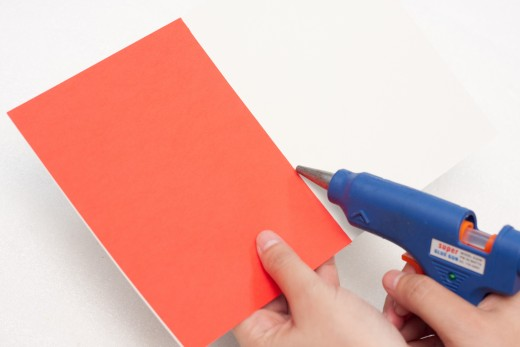 Cut a rectangle out of the red construction paper and glue it inside the card to make your card colorful and bright.