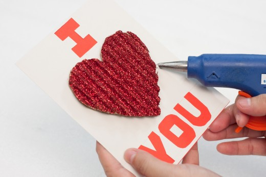 Place the glittery heart in the center of your card.  When you like the way it looks use your hot glue gun to glue the heart in that spot.