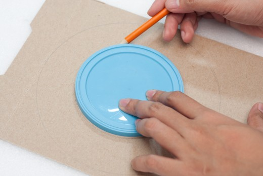 Trace a circle on a piece of cardboard (we used the front of a cereal box) Then draw a smaller circle in the center.  We used a bowl for the larger circle and a coffee can lid for the smaller circle