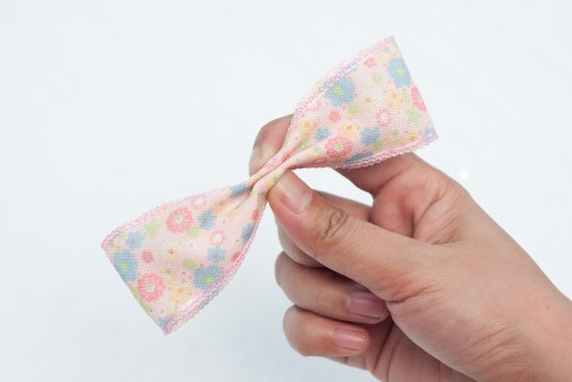 Pinch the center of the bow