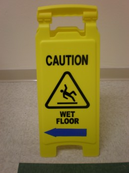 """A portable plastic sign warning of a wet floor that has recently been mopped."""