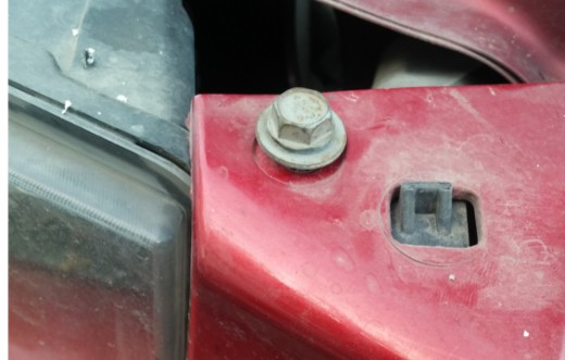 Screw under cosmetic cover.  Holds bumper on when all other nuts and screws are removed.