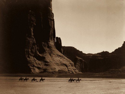 Canon de Chelly – Navajo. Seven riders on horseback and dog trek against background of canyon cliffs, by Edward S. Curtis 1904.