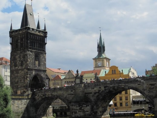The view on the Charles Bridge with the Old Town Tower made from a boat on the Vltava River
