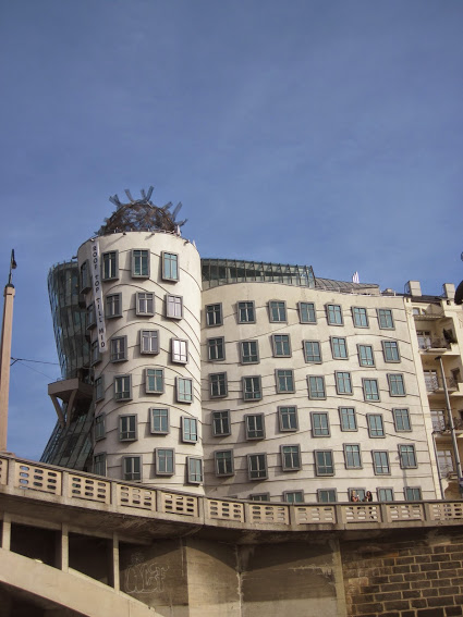 This is not a typical front view of the Dancing House, but its unique style is still visible even from this point of view