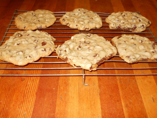 Remove cookies from oven. Slide the parchment paper off the sheet (with cookies). Leave until cookies are barely cool enough to handle. Then transfer to rack to cool some more.