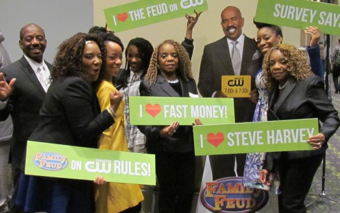 The Coleman Family, pose with a poster of Steve Harvey, host of Family Feud after their tryouts.