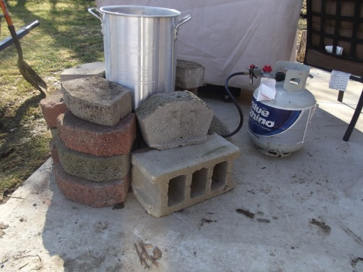 Turkey fryer surrounded by landscape bricks to retain heat better.