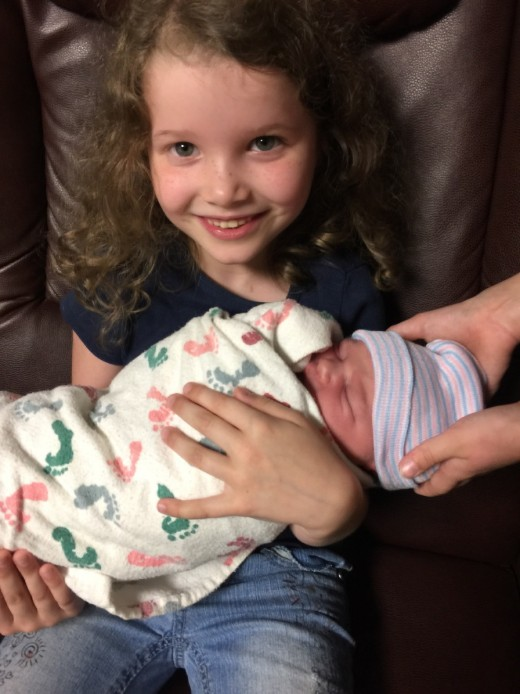 My granddaughter Lily holding my new grandson Charlie.