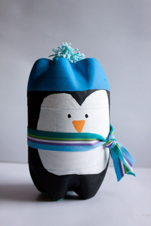 Two soda bottles, some paints, ribbon, and a pompom - plus some glue and patience - are what you need to make this little craft penguin project.