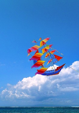 A pirate ship kite flying above the beach.