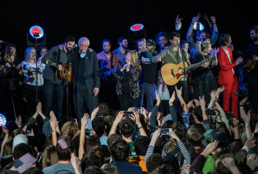 """Bernie performs """"This land is your land"""" with band Vampire Weekend."""