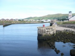 Looking into the harbour at Girvan. To the right is the Scottish Water building and, in the distance is the spire of the parish church with the Stumpy Tower further to the right of the picture.