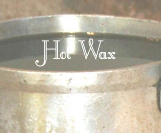 A small pot with melted hot wax