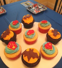 The table can be decorated with a dark blue tablecloth, Batman napkins, Justice League plates and a cupcake centerpiece.