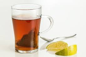 Lemon tea prepared dipping a teabag into hot water and mixing lemon juice in it.