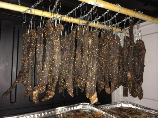 biltong hanging on hooks from the chain inside the biltong box