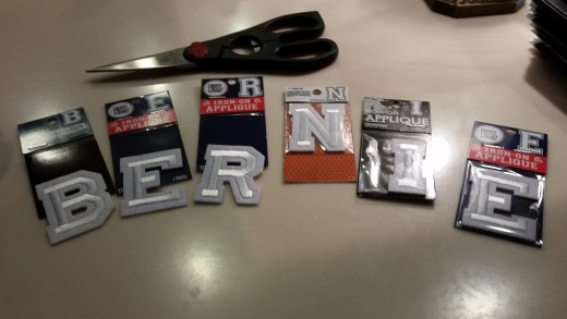 Find iron-on letters in the craft section at Walmart or a fabric store or craft store.