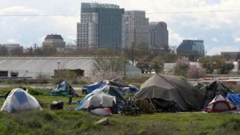 Tent city with skyline of Sacramento in the background