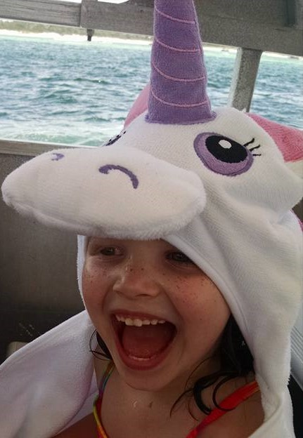 A child's smile is lovely.  Lily is so happy during their family time at the beach.