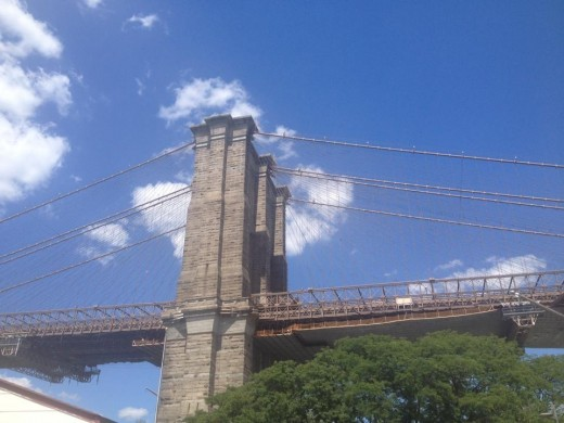 The iconic Brooklyn Bridge on a clear, sunny day.