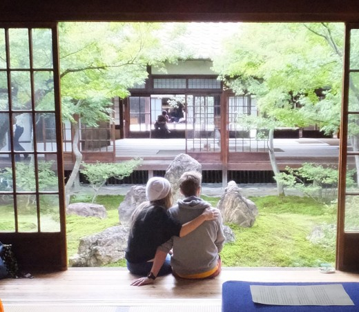 Two people, one with the arm around the other, sitting in a doorway overlooking a garden in Japan.