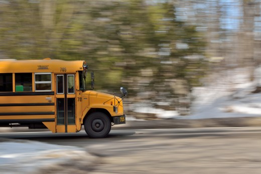 Image of the front part of a school bus driving on a road with a blurry background.