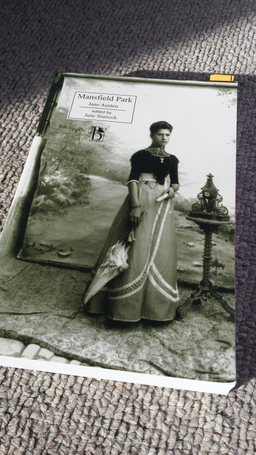 "Image of the Broadview edition of ""Mansfield Park"" sitting on the floor with a lady pictured on the cover in black-and-white."